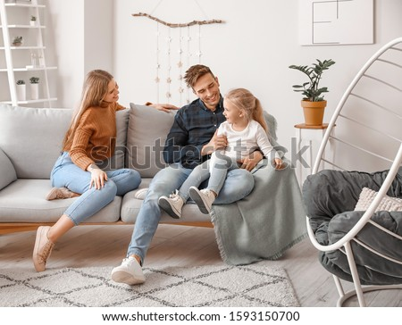 Happy young family sitting on sofa at home #1593150700
