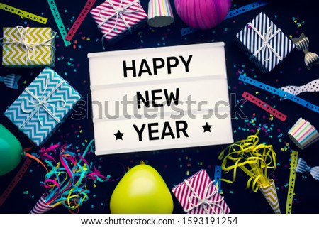 Celebration concepts with happy new year text on cinema light box and colorful element prop on dark background.funny and festival activity ideas #1593191254