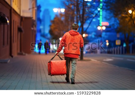 Young deliveryboy walking with red thermal bag on night city street. Man of delivery service in hurry to deliver an order. Delivery service goes to give the order quickly to the client at night #1593229828