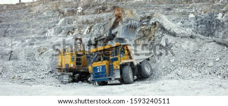Quarry dump truck against the background of an unsharp, in motion, heavy quarry excavator during the loading of stone ore in a limestone quarry, close-up panorama. #1593240511