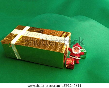 Real Gifts with Toy Santa in the picture stock photo.  Green background. Present wrapped in gold glitter paper. Celebration festive presents giving time. gift wrapped in gold glitter craft paper.