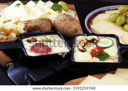 Delicious traditional Swiss melted raclette cheese on diced boiled or baked potato served in individual skillets with salami and potatoes #1593259768
