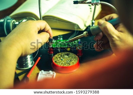 Hands of man holding solder iron  soldering the pin on electronics circuit board,  DIY hobbies and electrician workshop concept. #1593279388