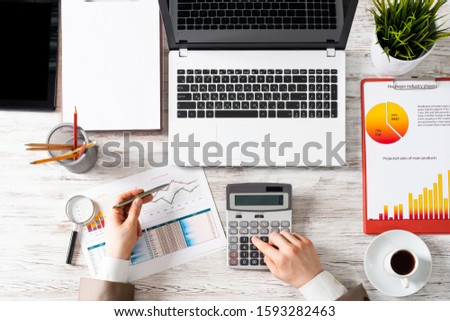 Businessman working at office desk with financial analytics. Top view office workplace with human hands calculating data. Flat lay table with laptop, calculator, business charts and cup of coffee. #1593282463