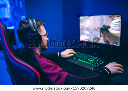 Professional gamer playing online games tournaments pc computer with headphones, Blurred red and blue background. #1593289240