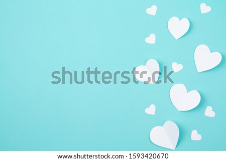 White paper hearts over the tuquiose background. Abstract background with paper cut shapes. Sainte Valentine, mother's day, birthday greeting cards, invitation, celebration concept #1593420670