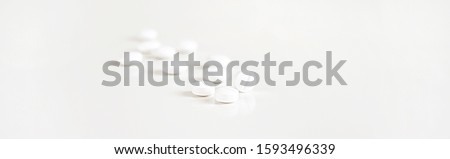 Medicine, pills. White pills on a light gray background. A scattering of tablets. Blurred background. Healthy lifestyle. Background for web site