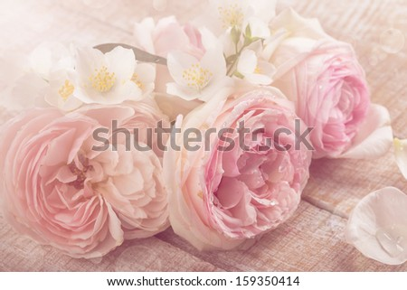Postcard with fresh pastel flowers - roses and jasmine on wooden background.