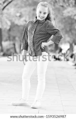 Never goes out of style. Adorable small girl wearing spotted shirt in street fashion style. Little cute child with long blond hair style on summer day. Casual is her style. #1593526987