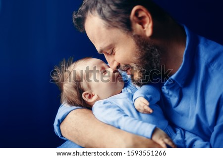 Middle age bearded Caucasian father hugging kissing newborn baby. Man parent holding child. Authentic lifestyle touching tender moment. Dad family life concept. Toned with classic blue 2020 color.  #1593551266