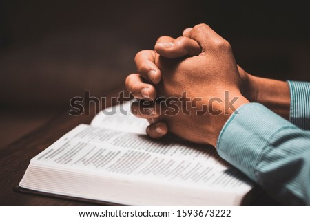 Man praying with his hands on a bible in church. #1593673222