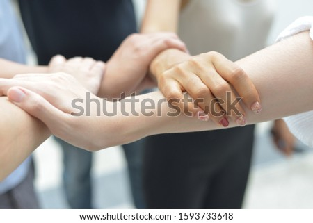 A group of close people grasping their arms together in a circle and showing solidarity and team work concept. #1593733648