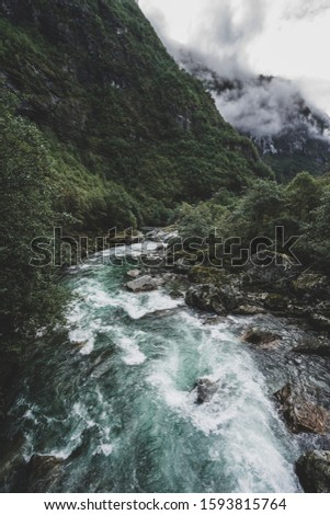 Wild and beautiful river in Norway with low, gray clouds, mountain and forest in background #1593815764