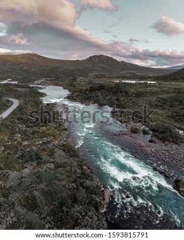 Aerial shot of a wild river with turquoise water and mighty waterfall in Norway, Jotunheimen National Park #1593815791