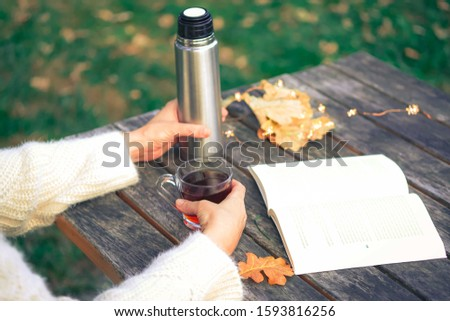 Cozy autumn tea break with a book, glasses, thermos flask,cup of tea and dry autumn leaves on old vintage wooden table. Cropped image of girl's hands waring warm knitted sweater, top view. #1593816256
