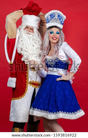 Emotional Santa Claus in a red coat and Snow Maiden in a blue suit posing on a red background #1593816922