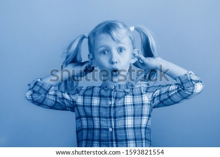 Funny Caucasian young girl making faces in front of camera. Child holding pulling dragging ears. Kid expressing emotions. April fool day concept. Toned with classic blue 2020 color. #1593821554