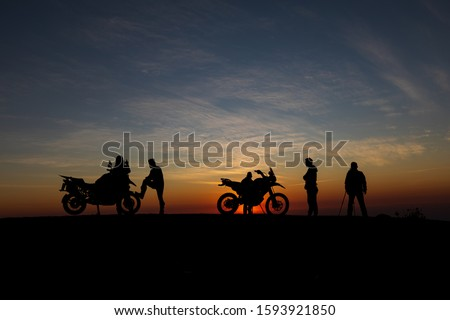 The peoples an acting for take photo with motocycle ,while sunrise behind on hight hill, is silhouette background