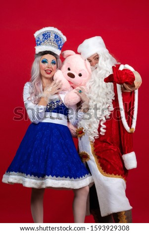 Emotional Santa Claus in a red coat and Snow Maiden in a blue suit posing on a red background #1593929308