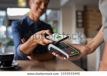 Woman paying bill through smartphone using NFC technology in a restaurant. Satisfied customer paying through mobile phone using contactless technology. Closeup hands of mobile payment at a coffee shop #1593933490