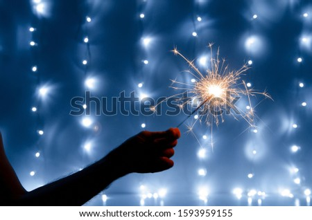 Hand holding sparklers on bokeh background. Abstract and brightly colorful firework in the celebration and anniversary festival.Merry Christmas and New year party #1593959155