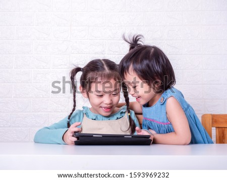 Two Asian little cute girl watching cartoon at tablet and smile. Happy two sisters use tablet for learning and entertainment.