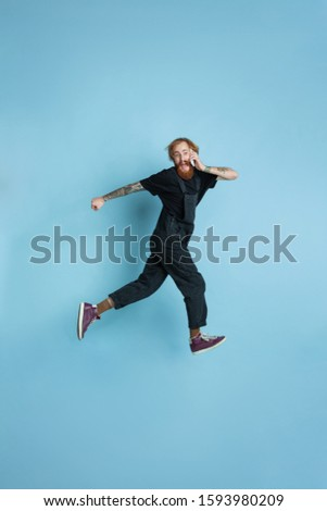 Portrait of young caucasian man looks dreamful, cute and happy. Jumping. laughting on blue studio background. Copyspace for your advertising. Concept of future, target, dreams, visualisation. #1593980209