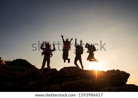 Climbing group friends jumping on top mountain and amazing sunset sky .Teamwork , Helps ,Success, winner and Leadership concept . #1593986617
