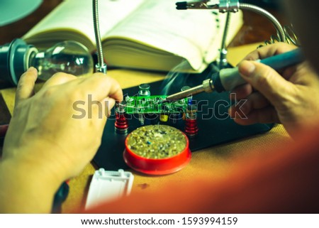 Hands of man holding solder iron  soldering the pin on electronics circuit board,  DIY hobbies and electrician workshop concept. #1593994159