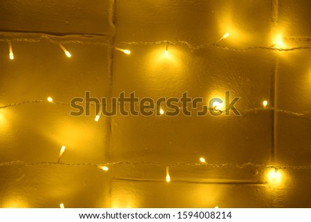 Christmas wall background decorated with glowing garlands of yellow color glows with beautiful reflections #1594008214