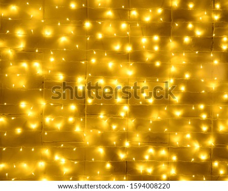 Christmas wall background decorated with glowing garlands of yellow color glows with beautiful reflections #1594008220
