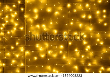 Christmas wall background decorated with glowing garlands of yellow color glows with beautiful reflections #1594008223
