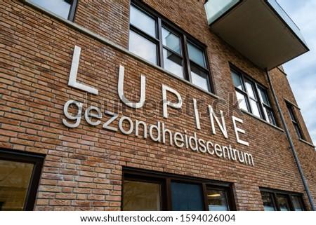 Alphen aan de Rijn, Netherlands, 12-20-2019.  The sign of the medisch centrum in Alphen aan de Rijn. A assembly building for doctors, pharmacy and dentist. Whit a cloudy sky. #1594026004