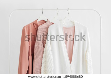 Feminine clothes in pastel pink  color on hanger on white background.  Elegant dress,  jumper, shirt and other fashion outfit. Spring cleaning home wardrobe. Minimal concept. #1594088680
