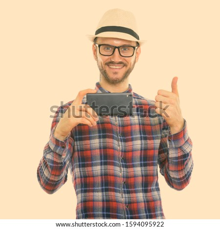 Studio shot of happy young man smiling while taking picture with mobile phone and giving thumb up