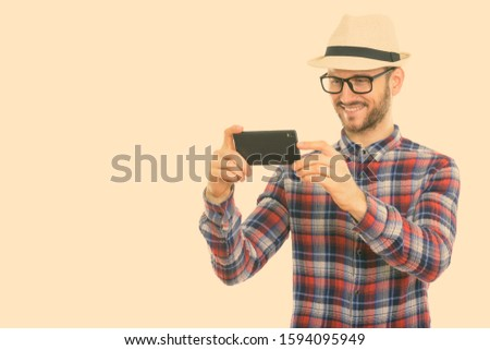 Studio shot of happy young man smiling while taking picture with mobile phone