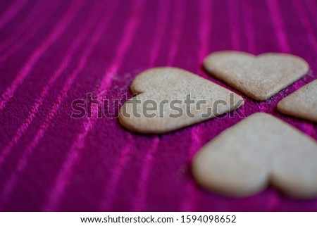 Heart-shaped cookies that in turn, together, make the shape of a four-leaf clover, isolated on a red background. #1594098652