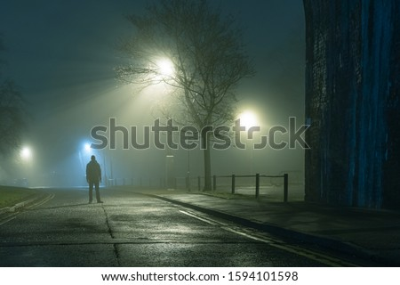 A mysterious figure standing by a city street light on a moody,  foggy atmospheric winters night #1594101598