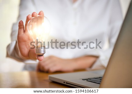 Business women holding light bulbs, ideas of new ideas with innovative technology and creativity. #1594106617