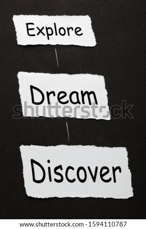 The words Explore, Dream and Discover on 3 piece of torn paper over black surface. #1594110787
