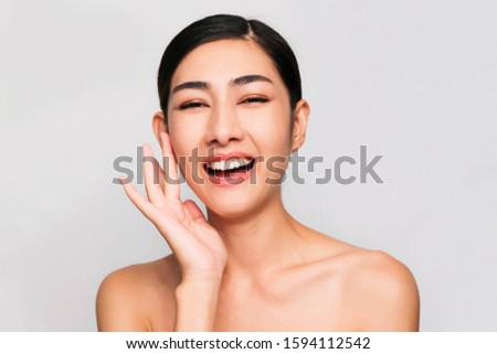 Young beautiful asian woman with clean and bright skin, Cosmetic Beauty Concept,hands touch on the cheek, smiling and friendly face isolated on grey background #1594112542