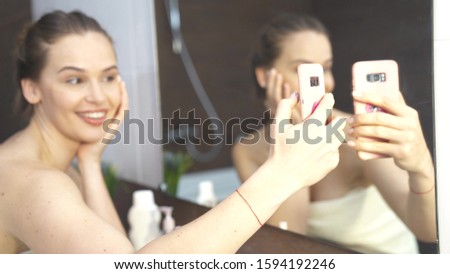 Young woman take mirror selfie at bathroom, side half length portrait. Finish morning routine and make picture using smartphone