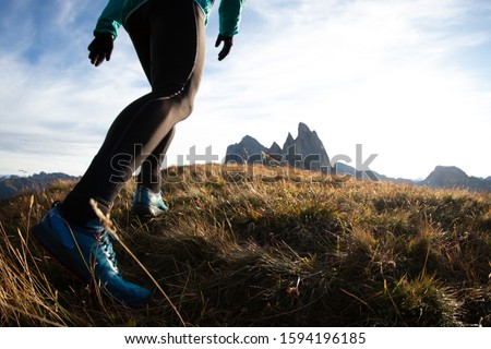 Young man in sport trail clothes running on Seceda mountain peak at sunrise. Puez Odle, Trentino, Dolomites, Italy. #1594196185