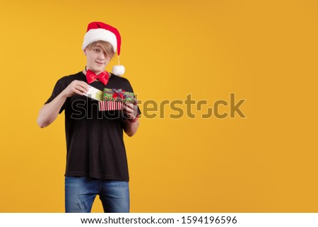 Young guy in a red Santa Claus hat holds in his hands banknotes, money and posing on a yellow background #1594196596