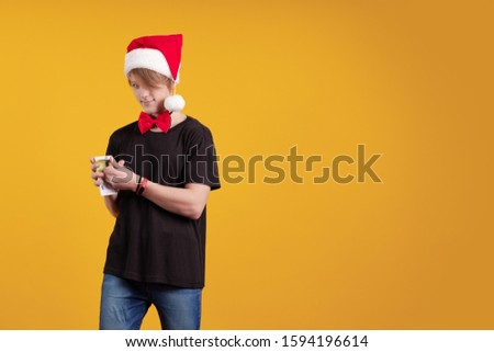 Young guy in a red Santa Claus hat holds in his hands banknotes, money and posing on a yellow background #1594196614