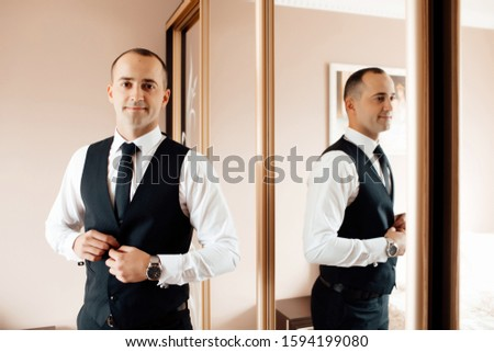 Preparations for the wedding. Fees of the groom. Wedding morning groom. Grooms morning preparation, handsome groom getting dressed and preparing for the wedding. The groom reflects in the mirror #1594199080
