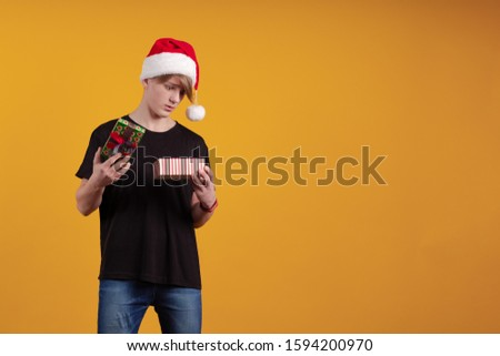 Young guy in a red santa hat holds a gift box in his hands and poses on a yellow background #1594200970