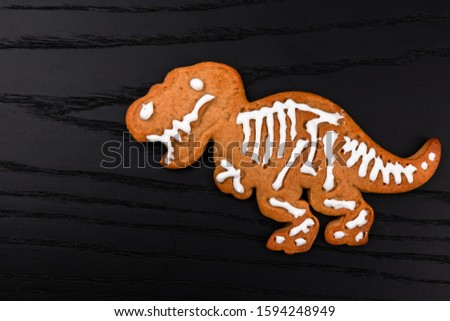 Homemade gingerbread cookie dinosaur Tyrannosaurus rex covered by white icing on black wooden background
