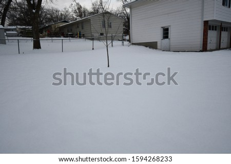 A house covered in snow following a blizzard in Kansas City, Missouri. Picture taken in December around sunset.