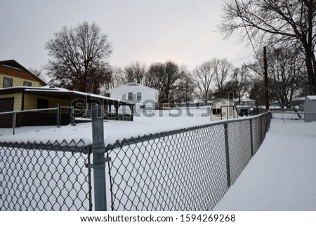 A house with a fence around the backyard. Snow is everywhere following a blizzard in Kansas City, Missouri. Picture taken in December around sunset.